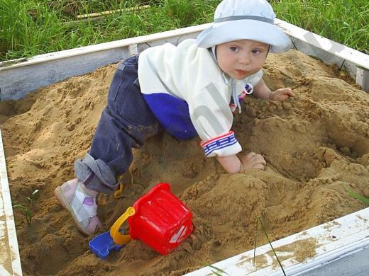 ребёнок ползает в песочнице