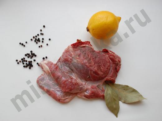 кусок свежей говядины с лимоном, перцем и лавровым листом