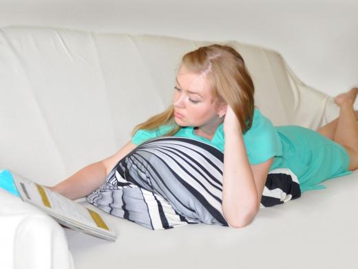 девушка читает журнал лёжа на животе